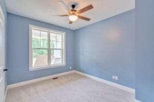 blue bedroom with big windows in custom home